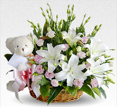 White carnations white lilies white Teddy 6 inches in same basket