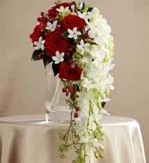 6 red roses with 10 white orchids drooping in a Vase