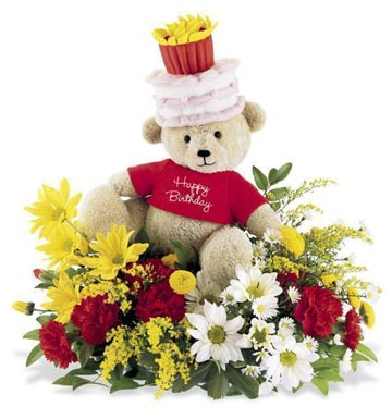 Teddy sitting in mix flowers basket