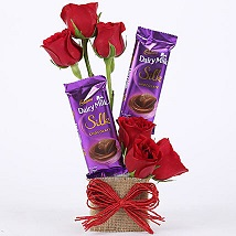 6 red roses with 2 Small Silk Chocolates in a basket tied with red ribbons